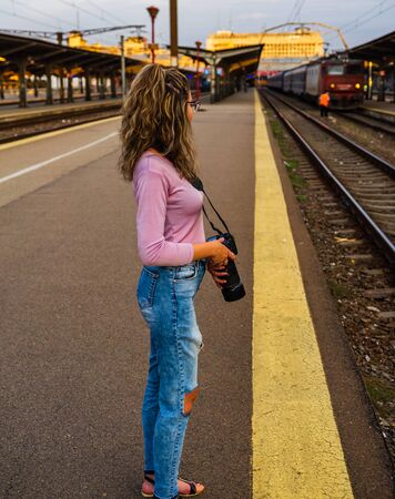 Young girl walking alone on train platform and taking photos on railway station Foto de archivo - 129990746