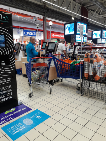 Sale, consumerism and people shopping concept - shopping cart at grocery store or supermarket in Bucharest, Romania, 2019