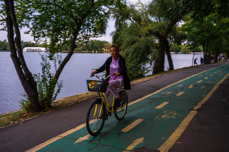 Girl riding a bicycle in King Mihai I park (Herastrau park) in Bucharest, Romania, 2019.