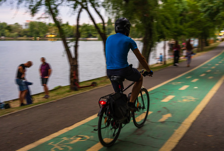 Man riding a bicycle in King Mihai I park (Herastrau park) in Bucharest, Romania, 2019.