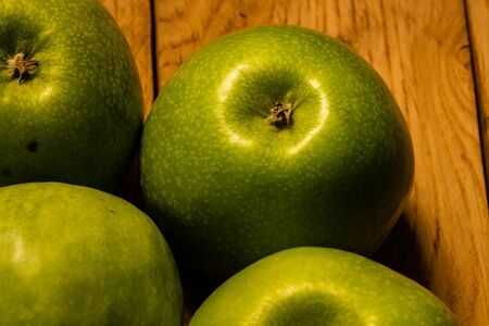 Close up photo of green apples on a wooden board. Stock fotó