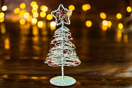 Christmas decorations against blurred background. Small silver wire Christmas tree. Mini Christmas tree.