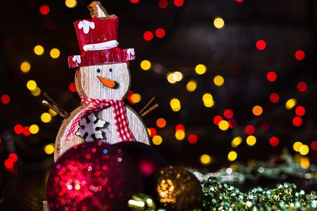Christmas decorations against blurred background and out of focus lights. Decorative wooden snowman and glittery Christmas balls