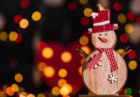 Christmas decoration and ornaments. Christmas composition on blurred lights background. Wooden Christmas snowman.