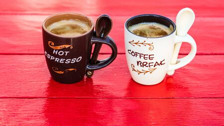 Two cups of homemade expresso coffee on red wooden board.