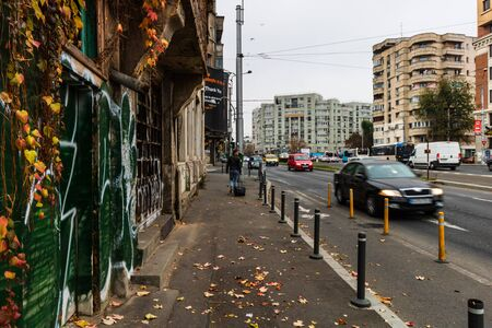 Man with carry on walking in the morning on the sidewalk in downtown Bucharest, Romania, 2019 에디토리얼