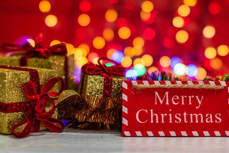 Merry Christmas wooden sign and glittery Christmas gifts. Christmas composition on blurred lights background. Stock Photo