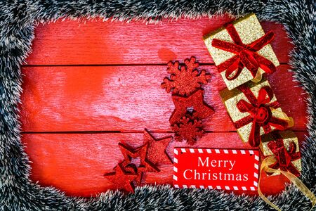 Christmas composition on red wooden board with Christmas garland and decorations. Creative composition with border and copy space, top view, flat lay. Christmas frame.