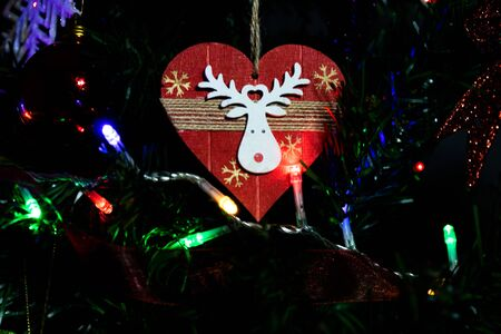 Christmas hanging decorations on fir tree. Decorated Christmas tree.  Fir branches with Christmas heart shaped decoration and lights. Stok Fotoğraf - 134768592