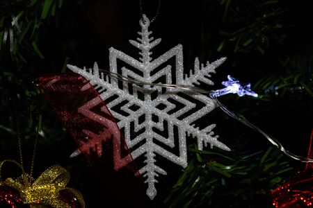 Christmas hanging decorations on fir tree. Decorated Christmas tree.  Fir branch with glittery Christmas snowflake. Stok Fotoğraf