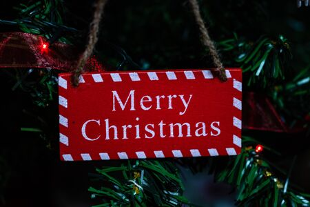 Christmas hanging decorations on fir tree. Decorated Christmas tree.  Fir branch with wooden merry christmas sign. Stok Fotoğraf