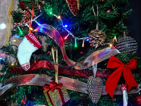Christmas hanging decorations. Decorated Christmas tree with balls, garlands and lights. Fir branches with Christmas decorations. Stok Fotoğraf - 134769326