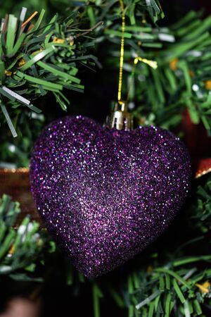 Christmas hanging decorations on fir tree. Decorated Christmas tree.  Fir branches with Christmas heart shaped decoration and lights. Stok Fotoğraf - 134769330