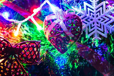 Christmas hanging decorations on fir tree. Decorated Christmas tree. Fir branch with Christmas decorations surrounded by lights and garlands. Stok Fotoğraf - 134769024