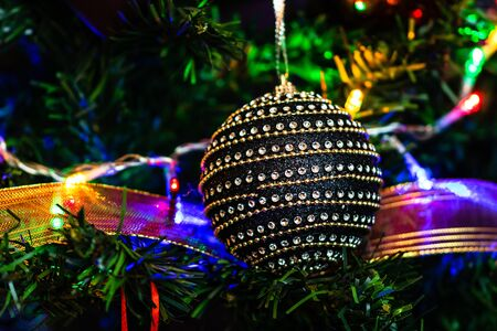 Christmas hanging decorations on fir tree. Decorated Christmas tree. Fir branch with black Christmas ball surrounded by lights and garlands. Stok Fotoğraf