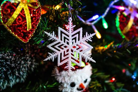 Christmas hanging decorations on fir tree. Decorated Christmas tree. Fir branches with glittery snowflake decoration. Stok Fotoğraf - 134769032