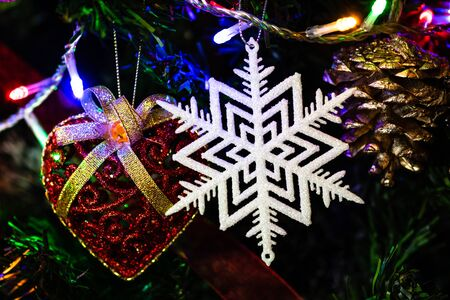 Christmas hanging decorations on fir tree. Decorated Christmas tree. Fir branches with glittery snowflake decoration.