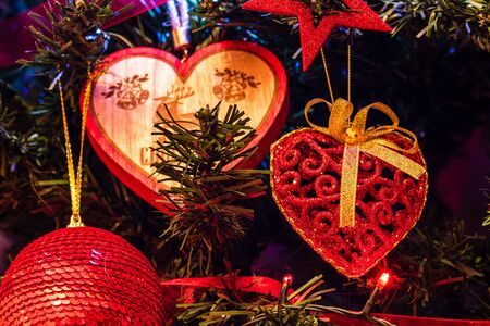 Christmas hanging decorations on fir tree. Decorated Christmas tree. Fir branch with Christmas heart shaped decoration.