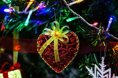 Christmas hanging decorations on fir tree. Decorated Christmas tree. Fir branch with Christmas heart shaped decoration. Stok Fotoğraf - 134768991