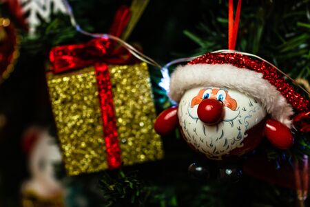 Christmas hanging decorations on fir tree. Decorated Christmas tree. Fir branches with Santa Claus figurine.