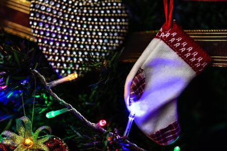 Christmas hanging decorations on fir tree. Decorated Christmas tree. Fir branch with Christmas stocking surrounded by lights and garlands. Stok Fotoğraf - 134768994