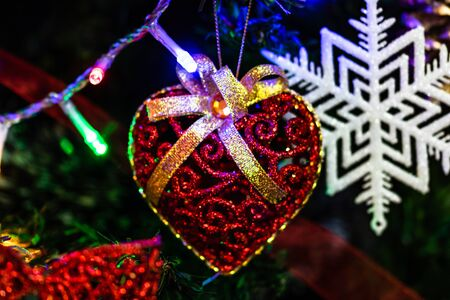 Christmas hanging decorations on fir tree. Decorated Christmas tree. Fir branch with Christmas heart shaped decoration. Stok Fotoğraf - 134768996