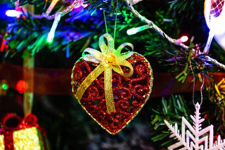 Christmas hanging decorations on fir tree. Decorated Christmas tree. Fir branch with Christmas heart shaped decoration. Stok Fotoğraf - 134768998