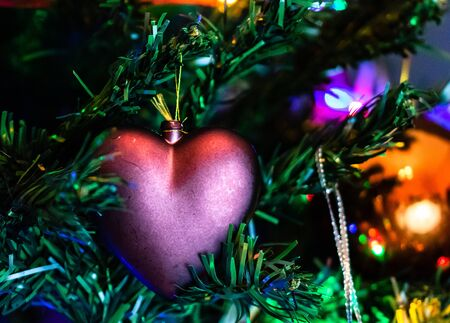 Christmas hanging decorations on fir tree. Decorated Christmas tree. Fir branch with Christmas heart shaped decoration. Stok Fotoğraf - 134769003
