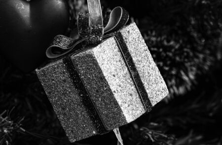 Christmas hanging decorations. Decorated Christmas tree. Fir branch with gift decoration. Black and white photo. Stok Fotoğraf