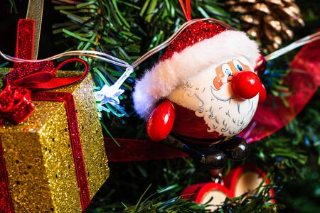 Christmas hanging decorations on fir tree. Decorated Christmas tree. Fir branches with Santa Claus figurine. Stok Fotoğraf - 134769006