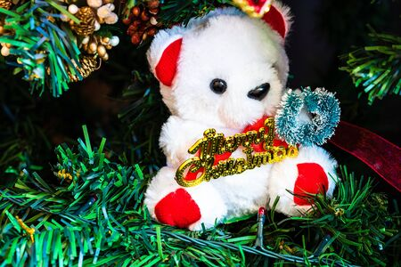Christmas hanging decorations on fir tree. Decorated Christmas tree. Fir branch with Christmas bear toy.