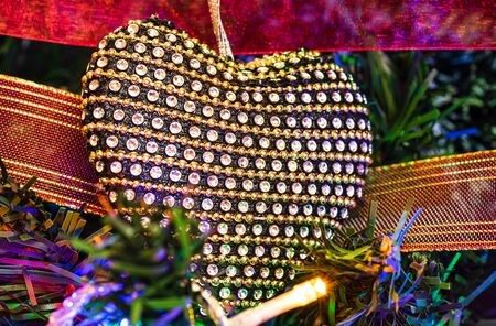 Christmas hanging decorations on fir tree. Decorated Christmas tree. Fir branch with Christmas heart shaped decoration surrounded by lights and garlands.
