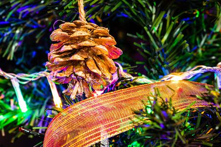 Christmas hanging decorations on fir tree. Decorated Christmas tree. Fir branches with pine cone surrounded by lights and garlands. Stok Fotoğraf - 134768943