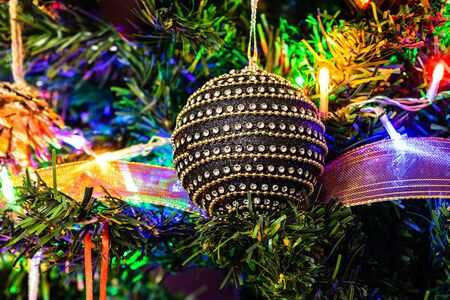 Christmas hanging decorations on fir tree. Decorated Christmas tree. Fir branch with black Christmas ball surrounded by lights and garlands. Stok Fotoğraf - 134768946