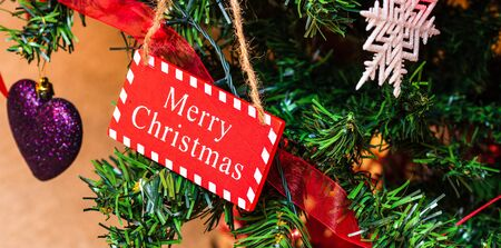 Christmas hanging decorations on fir tree. Decorated Christmas tree. Fir branch with wooden Merry Christmas sign.