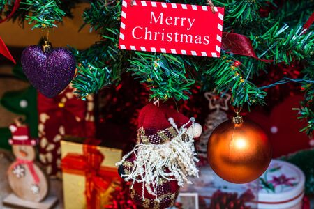 Christmas hanging decorations on fir tree. Decorated Christmas tree. Fir branch with wooden Merry Christmas sign. Stok Fotoğraf - 134768955