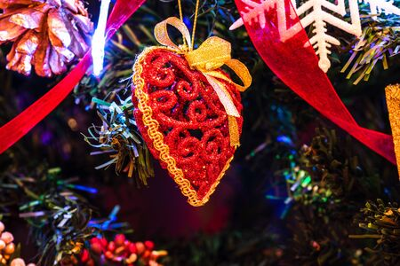 Christmas hanging decorations on fir tree. Decorated Christmas tree. Fir branch with Christmas heart shaped decoration. Stok Fotoğraf - 134768969