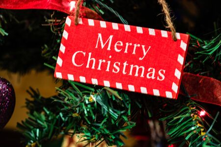Christmas hanging decorations on fir tree. Decorated Christmas tree. Fir branch with wooden Merry Christmas sign. Stok Fotoğraf - 134768872