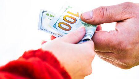Mano dando dinero como soborno o propinas aisladas, mano trabajadora tomando dinero en dólares. Transferencia de moneda sobre fondo blanco. Recompensa por el trabajo duro. Foto de archivo