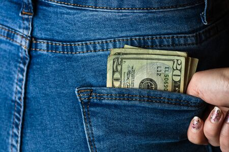 Teenage girl grabs dollar banknotes from her back pocket. Banknotes close up, money in a jeans pocket. Dollars stick out of the jeans pocket, money currency concept
