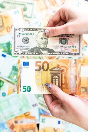 Hand holding money isolated on banknotes background. EURO and USD currency banknotes compared close up. Inflation, finance and business concept 版權商用圖片