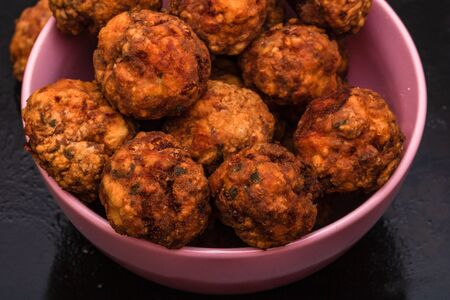 Pink bowl with fried meatballs with spices. Homemade food.