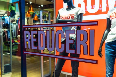 Discount (reduceri), sale signs, red poster offer, mock up advertise display frame over clothes in shopping mall or department store for show promotion product at AFI Cotroceni Mall from Bucharest, Romania, 2020