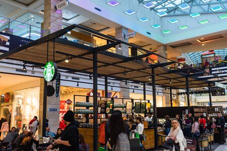 People sitting, waiting in line and working at the Starbucks at AFI Cotroceni Mall from Bucharest, Romania, 2020