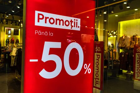 Discount, sale signs, red poster offer, mock up advertise display frame over clothes in shopping mall or department store for show promotion product at AFI Cotroceni Mall from Bucharest, Romania, 2020