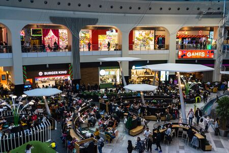 Shoppers visit the mall during winter at discount and sale season. Food court in AFI Cotroceni Shopping Mall in Bucharest, Romania, 2020