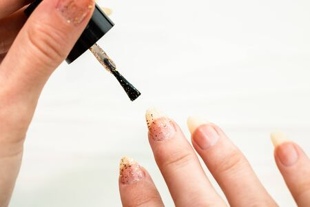 Female hands doing manicure, nail polish in gold glitter color on a white background. Skin and nail care salon concept Stok Fotoğraf