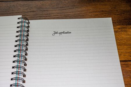 Job application, handwriting text on page of office agenda, office spiral notebook. Copy space.