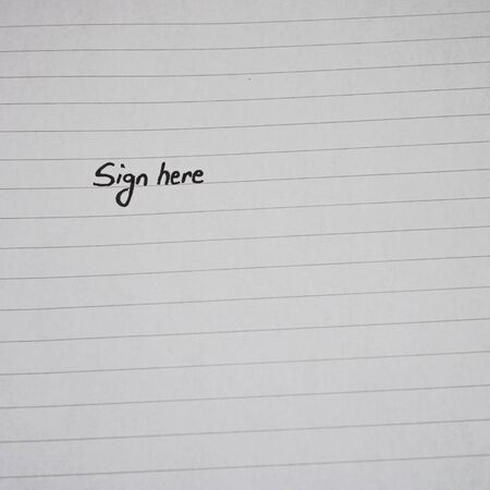 Sign here, handwriting text on page of office agenda, office spiral notebook. Copy space.