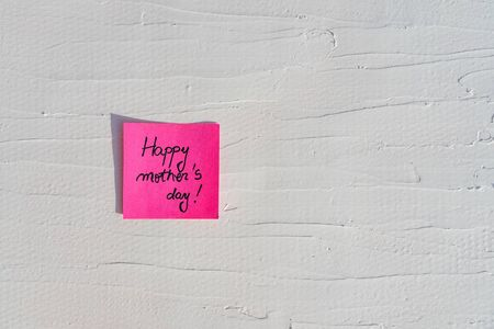 Handwriting text on memo post reminder. Happy mother`s day on paper, on white and textured wall.  Copy space. Stok Fotoğraf